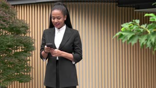 Successful Black Woman Talking On Cell Phone Near Office Building