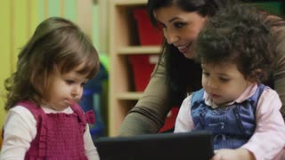 Teacher and little girls playing with ipad digital tablet computer in kindergarten