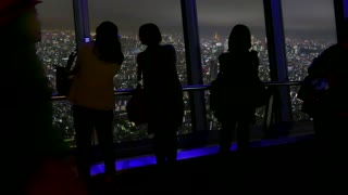 Tokyo, Japan, Asia. Aerial view of the city at night from Skytree tower. People, visitors, tourists looking at downtown buildings, neon lights. Asian and Japanese urban landscape