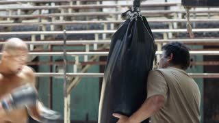 Trainer and black fighter exercising in boxing gym combat sports