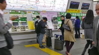 Undergound subway station, train, Japanese people commuting, Tokyo, Japan, Asia. Rush hour, railway gates, automatic vending machines and Asian commuters buying train tickets