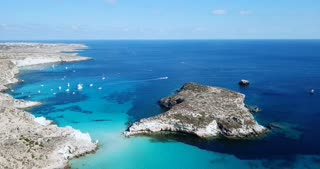 Aerial view of Isola dei Conigli next to the island of Lampedusa, Sicily, Italy with Mediterranean sea. Italian summer landscape seen from the sky with drone flying over beach