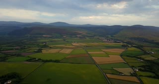 Aerial view of small farms and fields on Isle of Man. Nature, agriculture in countryside, landscape, natural beauty seen from drone flying in the sky