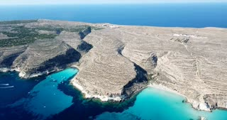 Aerial view of Spiaggia dei Conigli next to the island of Lampedusa, Sicily, Italy with Mediterranean sea. Italian summer landscape seen from the sky with drone flying over beach