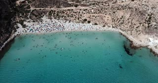 Aerial view of the island of Lampedusa, Sicily, Italy near Isola dei Conigli with Mediterranean sea. Italian beach with people swimming on holiday as seen from the sky with drone flying
