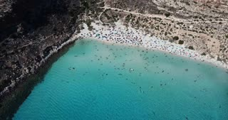 Aerial view of the island of Lampedusa, Sicily, Italy near Isola dei Conigli with Mediterranean sea. Italian beach with tourists swimming on vacation as seen from the sky with drone flying