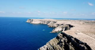 Aerial view of the island of Lampedusa, Sicily, Italy with Mediterranean sea. Italian natural landscape seen from the sky with drone flying over the rocky coast and cliffs