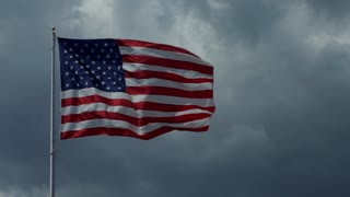 American flag flying with cloudy sky in the background. Stars and Stripes of the United States of America, symbol and concept of freedom, liberty, democracy. Copy space