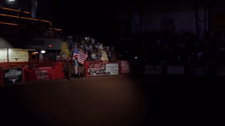 American girl riding horse at rodeo and holding US flag in Cowtown Coliseum, arena in the stockyards of Forth Worth, Texas, United States of America