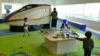 Asian children and family playing with toys in playground during visit at the Kyoto Railway Museum. Exhibition of Japanese wagons, coaches, trains and locomotives. Kyoto, Japan, Asia