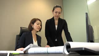 Asian people at work in architect office. Japanese business women working in engineer studio. Team of businesswoman and assistant looking at house plans during meeting