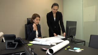 Asian people at work in executive office. Japanese business women working in corporate studio. Successful businesswoman talking to assistant and looking at house plans during meeting