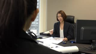 Asian people at work in executive office. Japanese business women working in corporate studio. Successful businesswoman talking to secretary during meeting for job interview