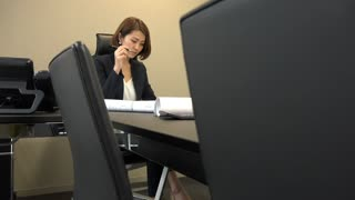 Asian people at work in office. Japanese business women working in studio with building projects. Confident businesswoman talking to secretary and looking at blueprints during meeting