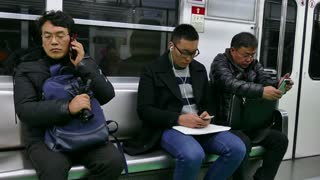 Asian people, Korean men with mobile phone, traveling on underground subway train. Seoul, South Korea, Asia