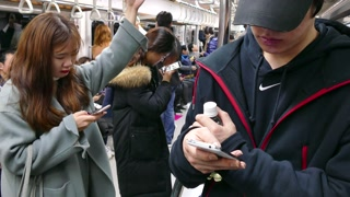 Asian people, Korean youth with smartphone, mobile telephone, cell phone for email, social media and internet, traveling on underground subway train. Seoul, South Korea, Asia
