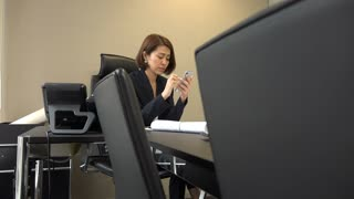 Asian people relaxing during break in office. Bored Japanese business woman texting message on cell phone. Tired businesswoman messaging with smartphone. Internet and technology