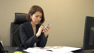Asian people relaxing during break in office. Bored Japanese business woman typing text message on mobile telephone. Tired businesswoman sending email with smartphone