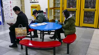 Asian people relaxing with mobile phone near readers corner in underground subway station. Seoul, South Korea, Asia