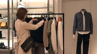 Asian people shopping for fashion goods and accessories. Japanese woman in luxury shop inside mall. Client buying new clothes in store and talking to sales manager for help and assistance