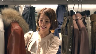 Asian people shopping for fashion goods and accessories. Japanese woman in luxury shop inside mall. Lady buying jacket and clothes in store