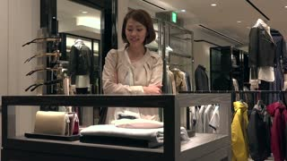 Asian people shopping for fashion goods and accessories. Japanese woman in luxury shop inside mall. Lady buying leather wallet in store and talking to sales assistant for help and assistance