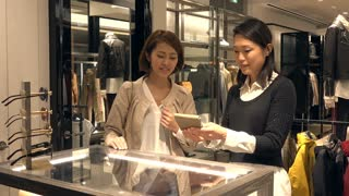 Asian people shopping for fashion goods and accessories. Japanese woman in luxury shop inside mall. Lady buying leather wallet in store and talking to sales manager for help and assistance