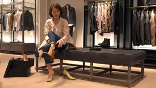 Asian people shopping for fashion goods and accessories. Japanese woman in luxury shop inside mall. Lady trying and buying new shoes in store