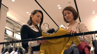 Asian people shopping for fashion goods and accessories. Japanese woman in luxury shop inside mall. Mom choosing boy jacket in store and talking to friendly sales manager for help and assistance