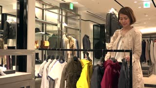 Asian people shopping for fashion goods and accessories. Japanese woman in luxury shop inside mall. Mother buying child jacket in store and talking to sales assistant for help and assistance