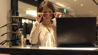 Asian people shopping for fashion goods and accessories. Japanese woman smiling in luxury shop inside mall. Happy lady trying and buying new sunglasses in store