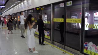 Asian people, tourists and Chinese commuters waiting for subway train arriving in underground station in Shanghai, China, Asia. Railway, transport, transportation, travel