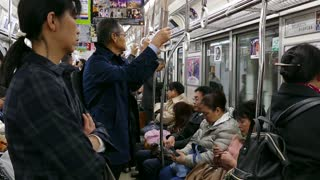 Asian people, tourists and Japanese commuters traveling on a subway train in Osaka, Japan, Asia. Railway, underground transport, transportation, travel