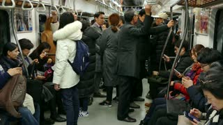Asian people, tourists and Korean commuters traveling on a crowded subway train in Seoul, South Korea, Asia. Underground railway, transport, transportation, travel during rush hour