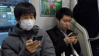 Asian people, young Japanese men with smartphone, mobile telephone, cell phone for email, social media and internet, traveling on local train. Tokyo, Japan, Asia