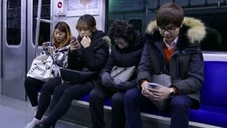 Asian people, young man and woman, Korean youth with mobile phone, traveling on underground subway train. Seoul, South Korea, Asia