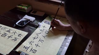 Asian teacher writing Chinese characters at calligraphy class. Man writing with brush, ink, and paper. School, education, culture, creativity