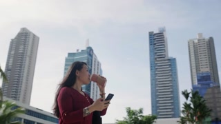 Asian Woman With Cell Phone Walking Near Office Buildings