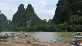 Beautiful Chinese natural landscape with karst hills, green mountains, countryside near Xingping, between Yangshuo and Guilin, China, Asia. Tourist ferry and boats during cruise on Li River