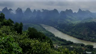 Beautiful Chinese natural landscape with karst hills, green mountains, small village, countryside near Xingping, between Yangshuo and Guilin, China, Asia. Tourist ferry boats during cruise on Li River