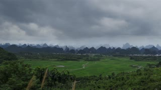 Beautiful Chinese natural landscape with karst hills, green mountains, small village, rice fields, countryside between Yangshuo and Guilin, China, Asia
