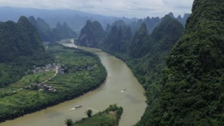 Beautiful Chinese natural landscape with karst hills, mountains, town and countryside between Yangshuo and Guilin, China, Asia. Tourist cruise ships on Li River, seen from Xianggong Hill viewpoint