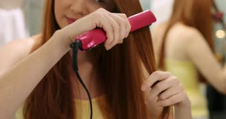 Beautiful Woman Straightening Healthy Red Hair With Iron Straightener