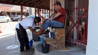 Black man cleaning and polishing cowboy boots of customer in the historic Stockyards district of Fort Worth, Texas, United States of America