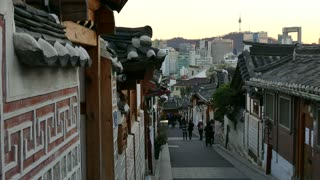 Bukchon Hanok Village, a Korean traditional village in Seoul, South Korea, Asia. Traditional houses (hanok) and modern buildings in the background at sunset
