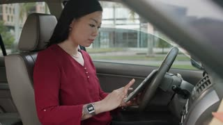 Busy Chinese Business Woman Working In Car With Papers