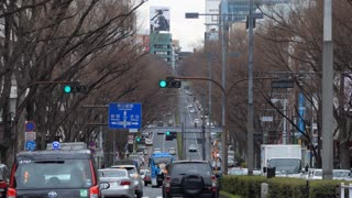 Cars driving on Omotesando street, Tokyo, Japan, Asia. Japanese avenue with traffic and people walking