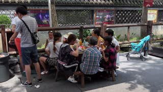 Chinese family eating at a restaurant selling traditional Asian food in Jinli old pedestrian street or Jin Li ancient street in Chengdu, Sichuan, China, Asia