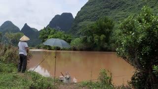 Chinese fisherman fishing for hobby and fun along Yulong river near Yangshuo, Guangxi, China, Asia