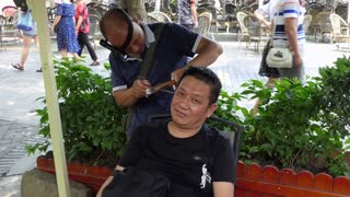 Chinese man practicing traditional ear cleaning and earwax removal on client in Jinli old pedestrian street in Chengdu, China, Asia. Male beauty, medicine, health therapy and body care
